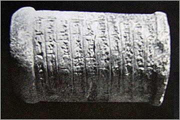 Επεξηγηματική πινακίδα από το μουσείο της Ενιγκάλντι με τη μορφή κυλίνδρου σε σφηνοειδή γραφή.
