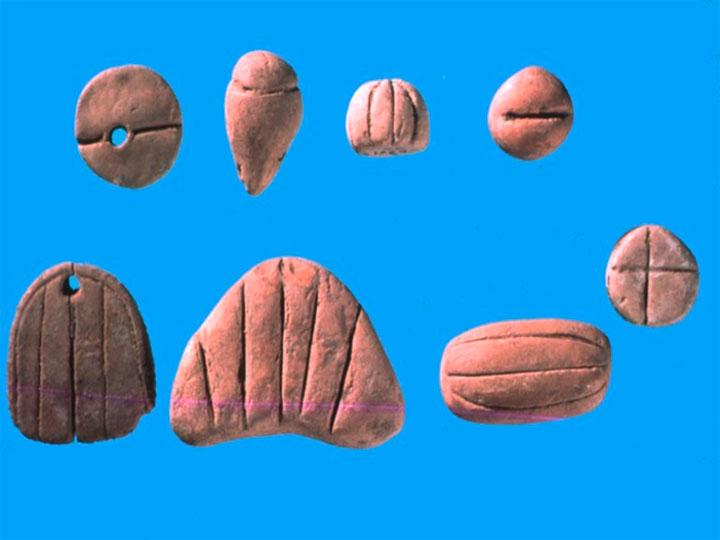Εικ. 12. Πέτρινα, κοκάλινα και πήλινα αντικείμενα που χαρακτηρίστηκαν ως tokens (μάρκες) από την ερευνήτρια της σουμεριακής  γραφής, D. Besserat, και θεωρήθηκαν στοιχεία ενός πρώιμου (του αρχαιότερου;) αλφαβήτου.