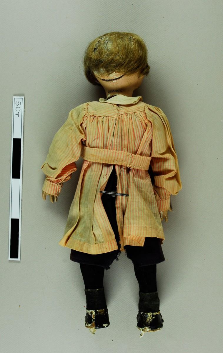 Εικ. 2. Π.Λ.Ι., αρ. ευρ. 2005.18.0004, «Τοto», η κούκλα πριν από τη συντήρηση (πίσω), στη μέση διακρίνεται το κουρδιστήρι.