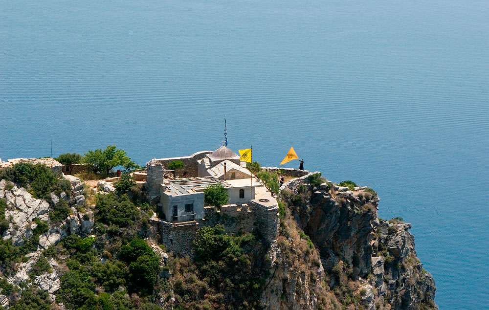 Εικ. 4. Στην άκρη του βράχου ένας μοναχός ανεμίζει μια μεγάλη κίτρινη σημαία με τον δικέφαλο αετό.