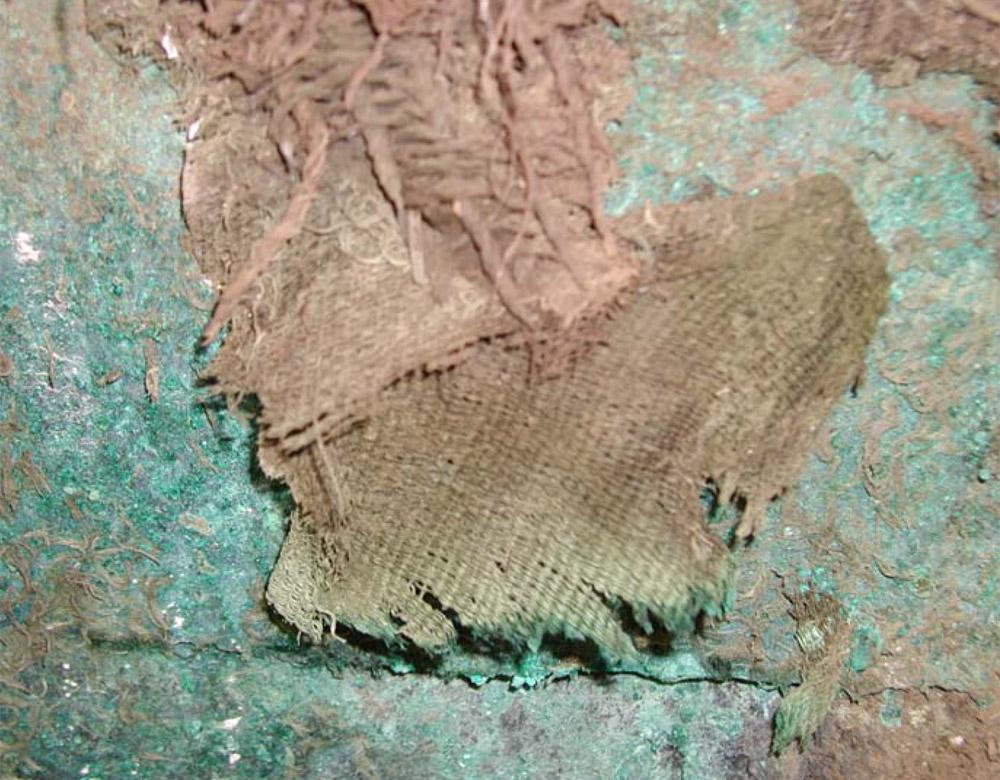 Εικ. 2. Λεπτομέρεια από το ταφικό σύνολο που περιλαμβάνει ύφασμα.Τα προϊόντα διάβρωσης του χαλκού έχουν διεισδύσει στο εσωτερικό των ινών, όπως διαφαίνεται και από το πράσινο χρώμα που αυτές έχουν αποκτήσει στο κάτω τμήμα του διατηρημένου υφάσματος.
