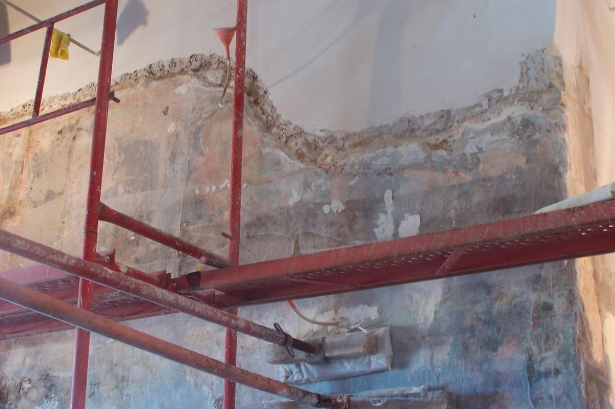 Εικ. 7. Τμηματική αφαίρεση παλαιών επεμβάσεων τσιμεντοκονίας, περιμετρικά των τοιχογραφιών:  οι στερεωμένες τοιχογραφίες πρεσάρονται με φύλλα καουτσούκ και οριζόντιες δοκούς (αρχείο Κ. Στουπάθη).