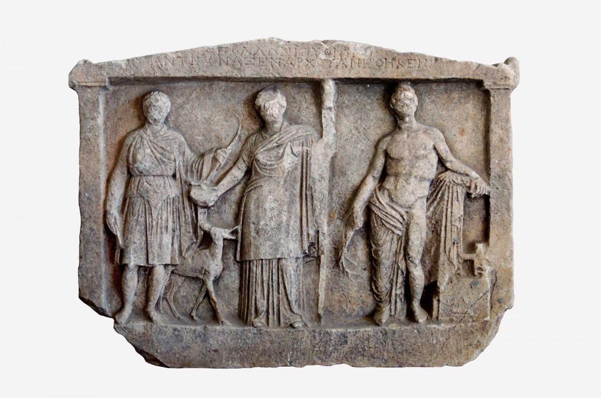 Εικ. 2. Αναθηματικό ανάγλυφο με παράσταση της Απολλώνιας τριάδας. Διαχρονικό Μουσείο Λάρισας, αρ. ευρ. Γ1.