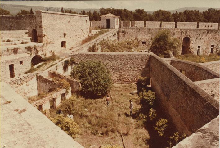 Εικ. 5. Ακρόπολη. Πανοραμική λήψη (1982) της ΒΑ πλευράς του αύλειου χώρου, με την αναβάθρα που οδηγεί στα περιπόλια, τους τοίχους των ακτίνων και τα μαγειρεία των φυλακών κάτω αριστερά.