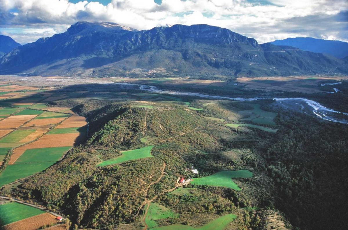 Εικ. 3. Το δυτικό τμήμα του κάμπου της Κόνιτσας, όπου διακρίνονται ο λόφος του Λιατοβουνίου στο κέντρο, η σμίξη των ποταμών Αώου και Βοϊδομάτη στα δεξιά, το όρος Γκαμήλα-Τύμφη στο βάθος. (Πηγή: Π. Τσιγκούλης)