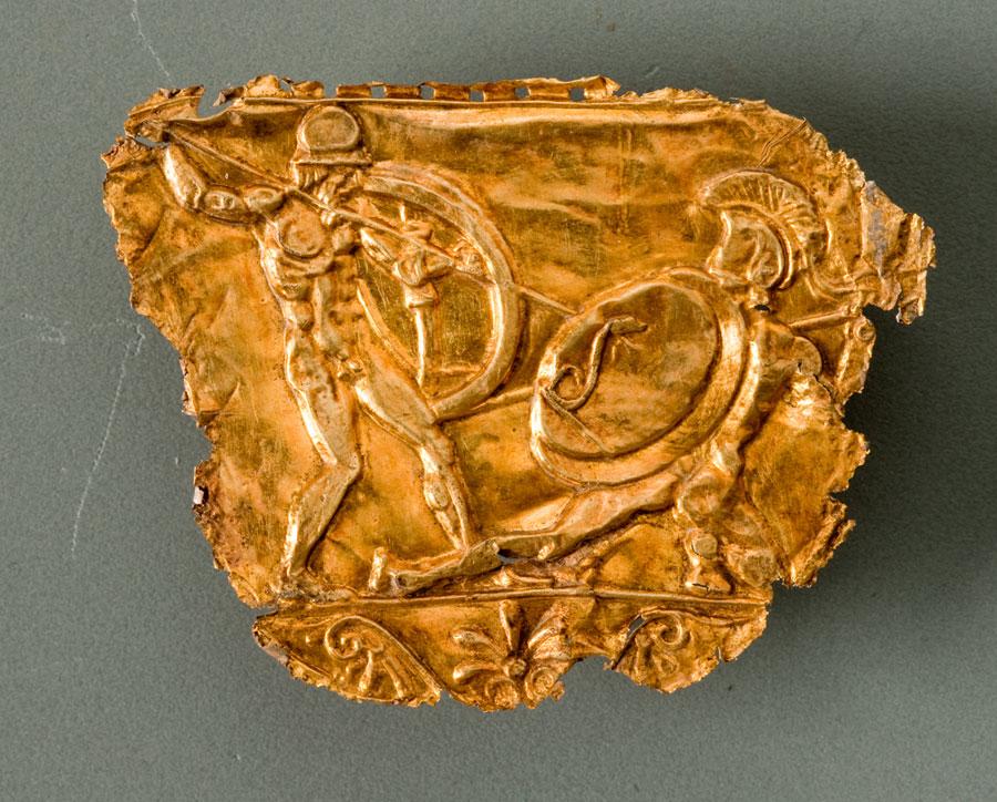 Χρυσό ανάγλυφο με πολεμιστές, προερχόμενο από τη διακόσμηση χρυσοποίκιλτης ασπίδας, που εντοπίστηκε στις Αιγές (φωτ. ΙΖ' ΕΠΚΑ).