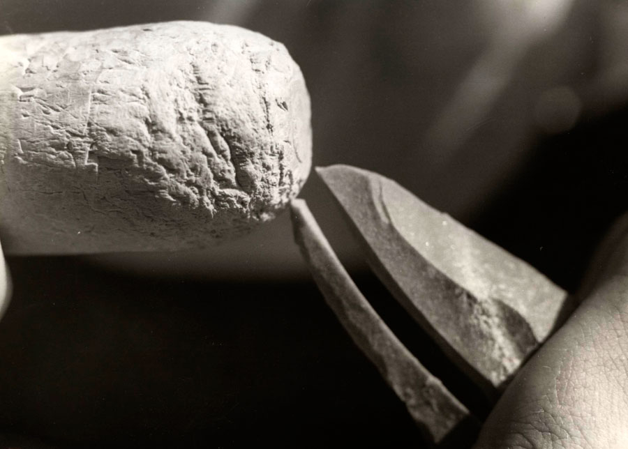 Εικ. 4. Απόσπαση με ξύλινο κρουστήρα (άμεση ελαστική κρούση) της επιμήκους μικρολεπίδος γλυφίδας (κάτω) και δημιουργία του «δοντιού» και του διέδρου της γλυφίδας (πάνω) σε λεπίδα πυριτολίθου (Πειραματική Αρχαιολογία) (φωτ. Αμαλία Καλαμαρά).