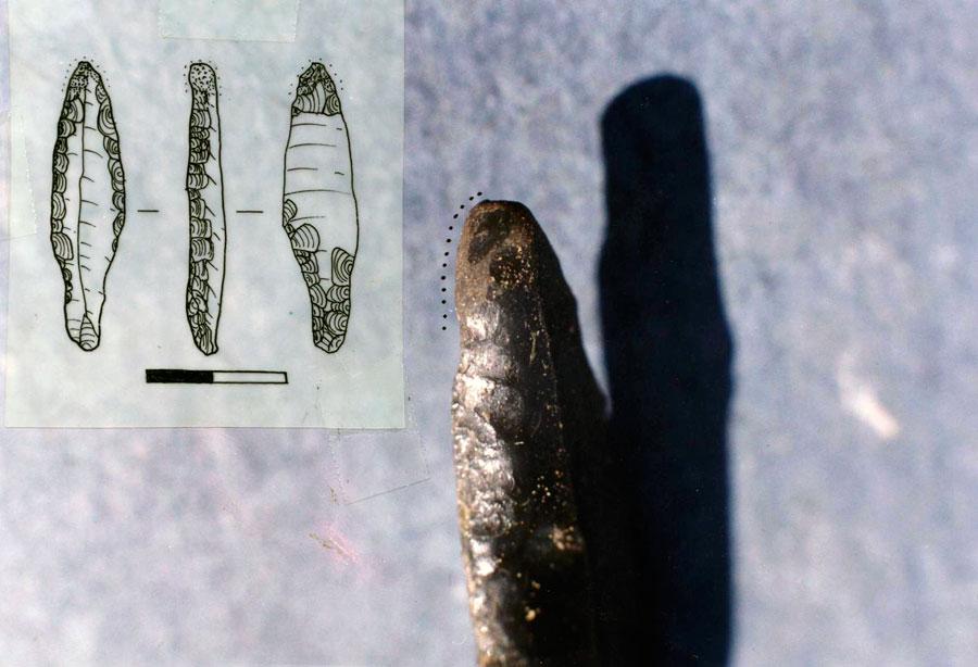 Εικ. 11. Αιχμή με μίσχο από οψιανό που προέρχεται από τη χαλκολιθική θέση του Αγίου Δημητρίου Λεπρέου Ηλείας (Λ1279). Στην απόληξή της και συγκεκριμένα στις πλευρές όπου η τριβή είναι μεγαλύτερη έχει εμφανέστατα ίχνη χρήσης (θαμπάδα) που υποδηλώνουν ότι είχε χρησιμοποιηθεί, ίσως σε δεύτερη χρήση, σαν αιχμή συμπαγούς τρυπανιού για τη διάτρηση σκληρών υλών. Φωτογραφική λεπτομέρεια της αιχμής και τμήματος της αριστερής πλευράς.