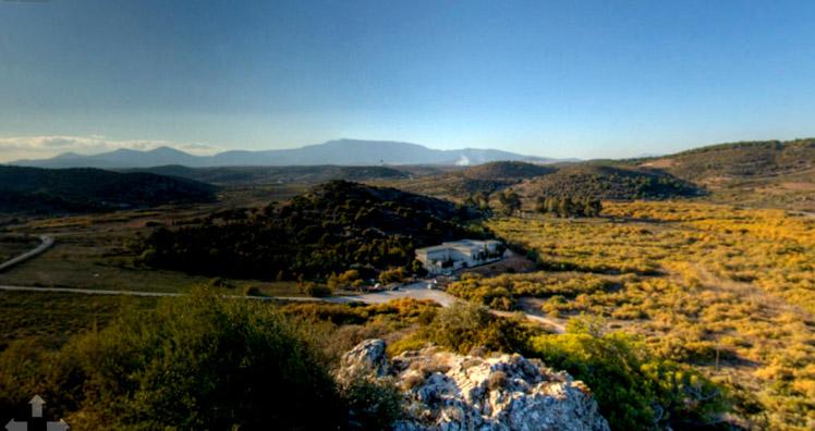 Εικ. 5. Η πλούσια φύση της περιοχής. Άποψη του λόφου της ακρόπολης και του μουσείου από τα νότια. Εικόνα από το Virtual Tour, που είναι διαθέσιμο στην ιστοσελίδα της ΕΟΕ.