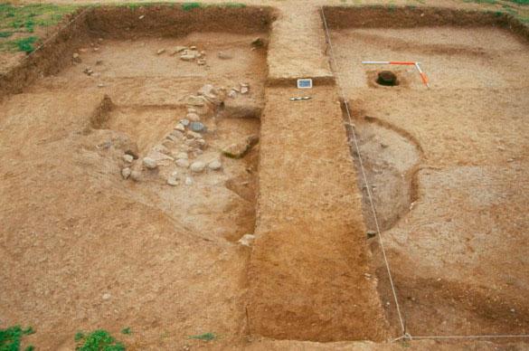 Εικ. 3. Οικιστικός λάκκος. Στο κέντρο ο μάρτυρας που δεν έχει ανασκαφεί, ενώ στο βάθος διακρίνεται η εστία.