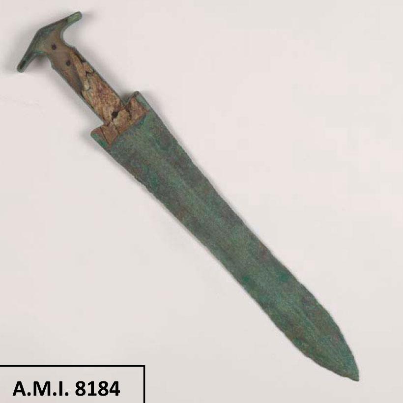 Χάλκινο εγχειρίδιο, τύπου F της Sandars, το οποίο φέρει εγχάρακτη σπειροειδή διακόσμηση και διατηρεί τμήμα της ελεφαντοστέινης επένδυσης της λαβής του. Από τον λακκοειδή τάφο 59, στο Λιατοβούνι Κόνιτσας (φωτ. ΙΒ΄  ΕΠΚΑ).