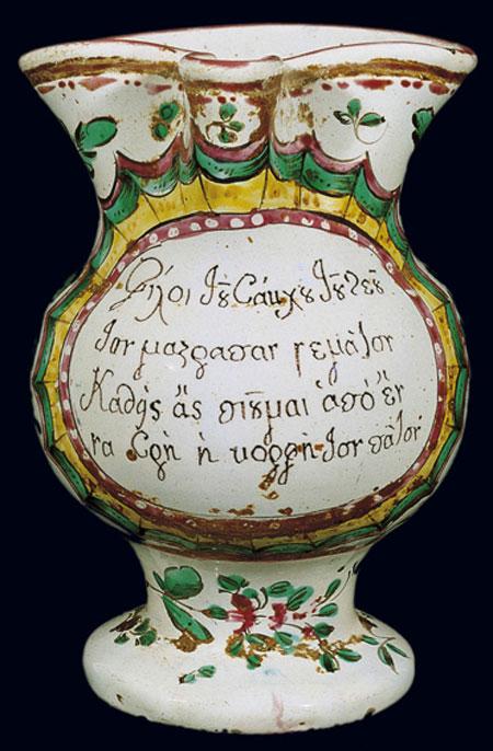 Κανάτι του κρασιού διακοσμημένo με άνθη και ελληνικούς βακχικούς στίχους. Ιταλικού εργαστηρίου (Pesaro), 18ος αι., για την ελληνική αγορά (αρ. ευρ. 8603). © Μουσείο Μπενάκη, Αθήνα.