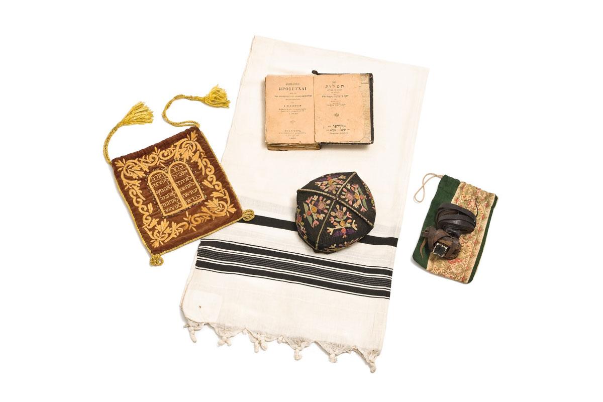 Εικ. 3. Η εξάρτυση ενός Μπαρ Μιτσβά περιλαμβάνει ένα Ταλέθ (σάλι προσευχής) με τη θήκη του, ένα Τεφιλίν (φυλακτήρια), μια Κιπά (σκούφος προσευχής) και ένα Σιντούρ (προσευχολόγιο για τις καθημερινές προσευχές). 19ος-αρχές 20ού αι. (© Εβραϊκό Μουσείο Ελλάδος, 2014).