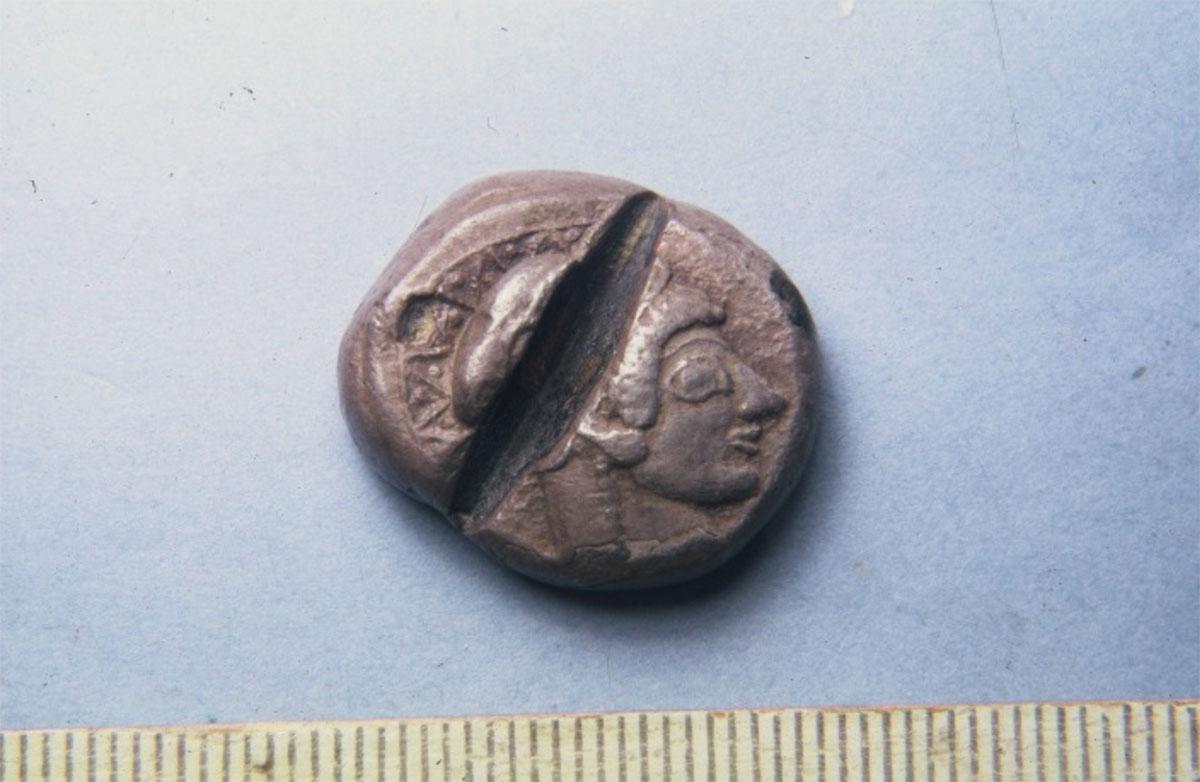 Εικ. 6. Κίβδηλο αθηναϊκό νόμισμα του 6ου αι. π.Χ.  Ήταν επαργυρωμένο χάλκινο νόμισμα, το οποίο χαράχτηκε ως κίβδηλο από τον αρχαίο δοκιμαστή (Νομισματικό Μουσείο Αθηνών).