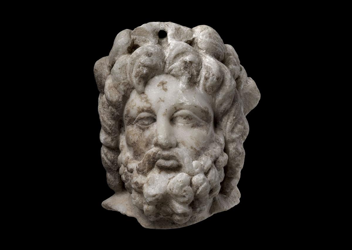 Εικ. 1. Μαρμάρινη κεφαλή γενειοφόρου στεφανωμένου θεού, ρωμαϊκών χρόνων (φωτ. ΛΒ᾽ ΕΠΚΑ).