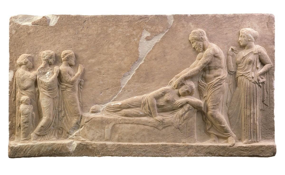 Μαρμάρινο αναθηματικό ανάγλυφο: Υπό το βλέμμα της Υγιείας, ο Ασκληπιός θεραπεύει την ξαπλωμένη ασθενή κατά τη διάρκεια της εγκοίμησης στο Ασκληπιείο. Περ. 400 π.Χ., Αρχαιολογικό Μουσείο Πειραιά. © ΥΠΠΟΑ – ΚΣΤ΄ΕΠΚΑ (φωτογρ. αρχείο)