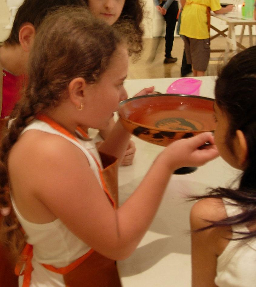 Εικ. 2. Τα παιδιά βιώνουν την εμπειρία της χρήσης της κύλικας με τη βοήθεια αντιγράφου (Εκπαιδευτικό πρόγραμμα «Χαίρε και πίει ή αλλιώς στην υγειά μας», Φωτογραφικό Αρχείο Εθνικού Αρχαιολογικού Μουσείου).