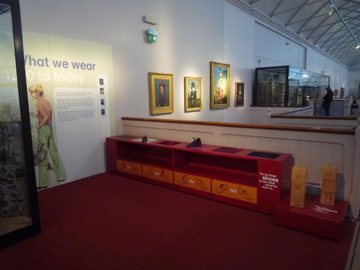 Εικ. 3. Μουσείο Παιδικής Ηλικίας V&A, Λονδίνο. Στο πλαίσιο της έκθεσης παιδικών φορεσιών από το 1700 έως σήμερα υπάρχει ενσωματωμένο διαδραστικό έκθεμα, στο οποίο τα παιδιά μπορούν να αγγίξουν υφές και να δοκιμάσουν παπούτσια διαφορετικών εποχών (Φωτογραφικό Αρχείο Δ. Καλεσοπούλου).