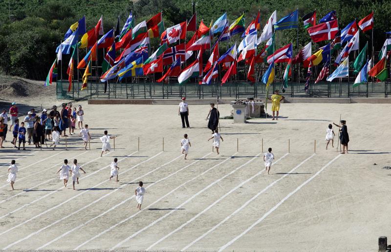 Νεαρά ποδαράκια ανασηκώνουν αρχαία σκόνη στο τέλος του αγώνα δρόμου. Οι σημαίες αντιπροσωπεύουν τις χώρες όσων συμμετείχαν στη Πέμπτη Νεμεάδα, Ιούνιος 2012.