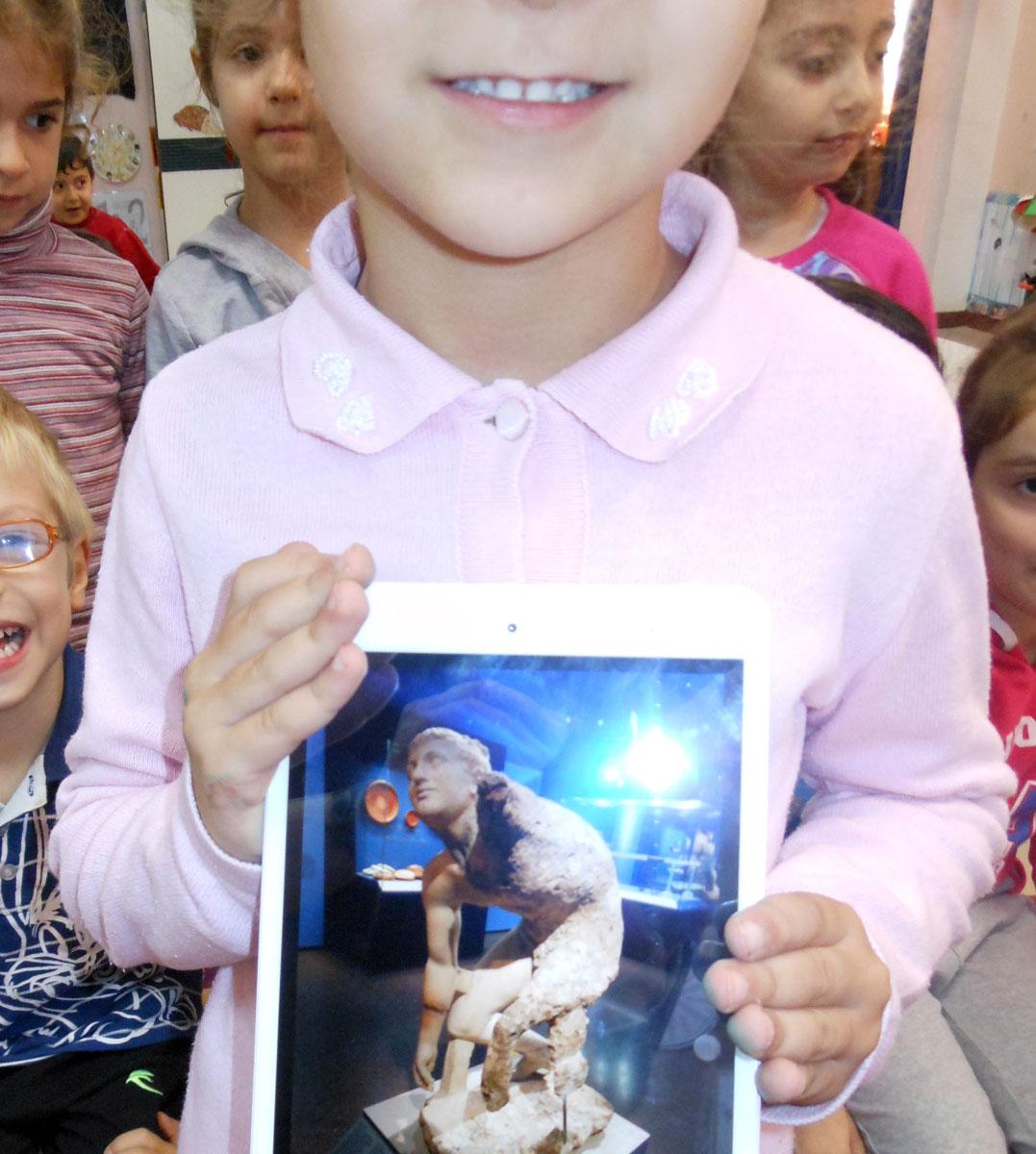 Εικ. 6.  Στιγμιότυπο δραστηριοτήτων διάχυσης των καλών πρακτικών, όπου τα παιδιά παρουσιάζουν μέσω tablet, σε εκδήλωση με γονείς, φωτογραφικές λήψεις από την έκθεση το «Ναυάγιο των Αντικυθήρων». Πρόγραμμα μύησης των νηπίων στις φυσικές επιστήμες και την τεχνολογία στο πλαίσιο της ερμηνείας μουσειακών αντικειμένων, με την έγκριση του Τμήματος Πολιτιστικών Θεμάτων της Διεύθυνσης Πρωτοβάθμιας Εκπαίδευσης Ανατ. Αττικής (αρχείο Β. Δεληγιαννίδη).