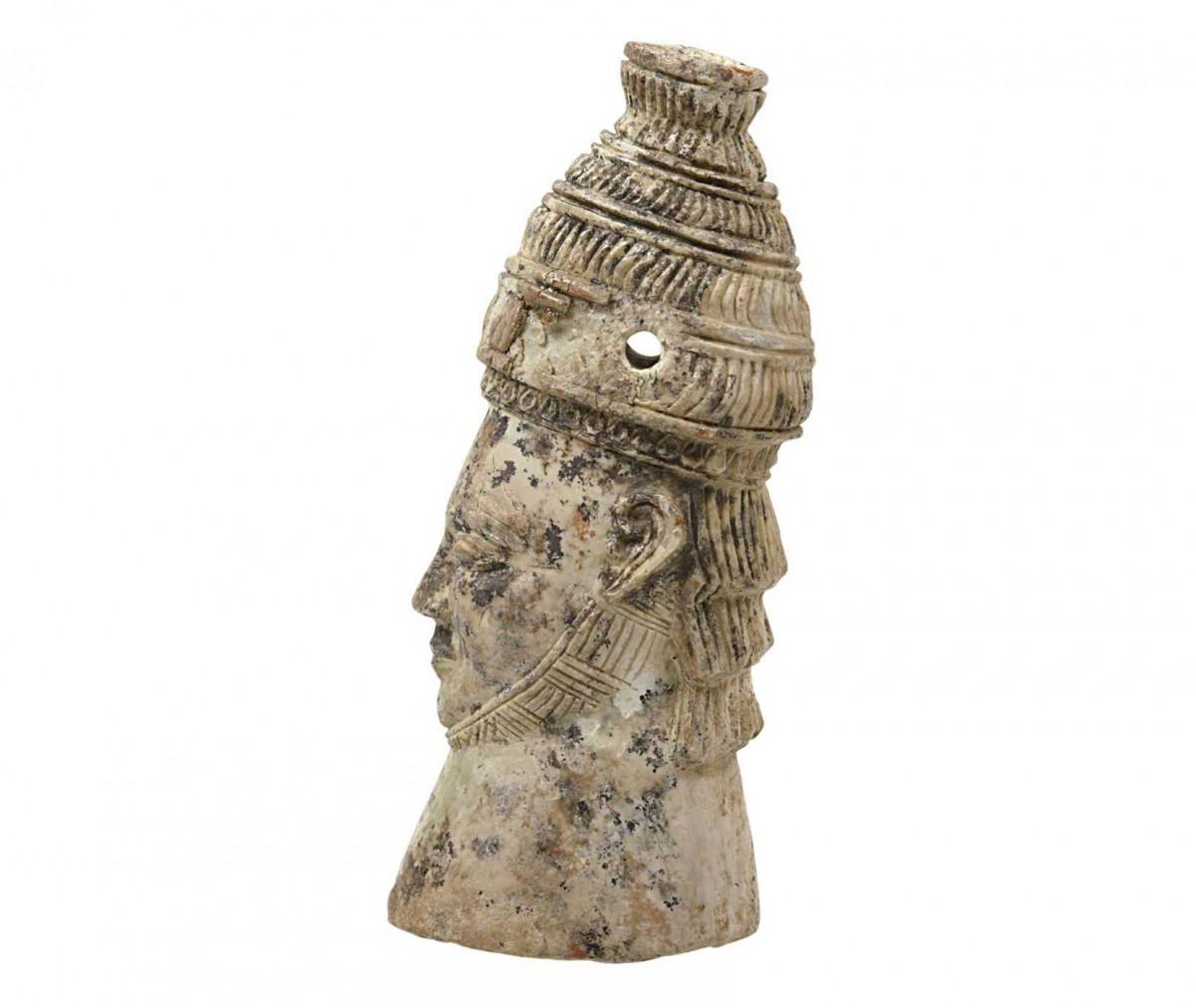 Ανάγλυφο πλακίδιο σε σχήμα κεφαλής άνδρα που φορά οδοντόφρακτο κράνος. Έκθεση Μυκηναϊκών Αρχαιοτήτων, αίθουσα 3, προθήκη μ2 (Εθνικό Αρχαιολογικό Μουσείο, αρ. ευρ. 2055).