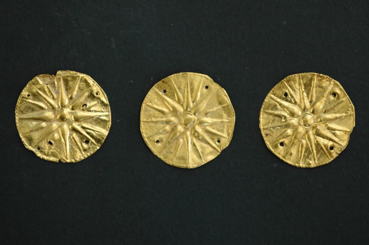 Εικ. 8. Αιανή. Βασιλική Νεκρόπολη, τάφος Α, χρυσοί ρόδακες. Η παρουσία στην Αιανή δειγμάτων του δεκαεξάκτινου χρυσού ρόδακα, που παριστάνουν το γνωστό μακεδονικό αστέρι, το σύμβολο του μακεδονικού βασιλείου του κράτους των Αιγών, αποδεικνύει τους δεσμούς και τις στενές σχέσεις που είχαν οι δύο πρωτεύουσες.