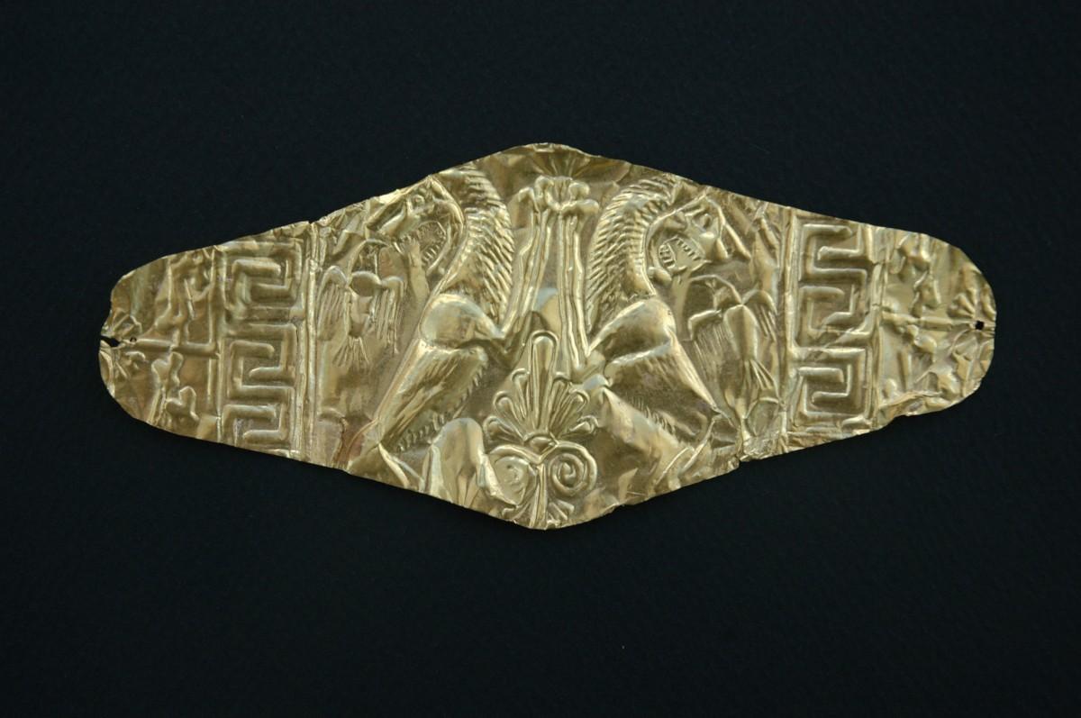 Εικ. 7.  Αιανή. Βασιλική Νεκρόπολη, χρυσό επιστόμιο. Ρομβοειδές έλασμα με έκτυπη παράσταση ανθεμίου, δύο λιονταριών, δύο αετών και μαιάνδρου. Τα επιστόμια, χρυσά ή αργυρά κάλυπταν το στόμα των νεκρών.