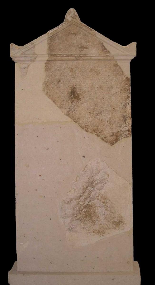 Λίθινη αετωματική ενεπίγραφη στήλη, που βρέθηκε το 1977, στον περίβολο του ναού του Απόλλωνα, στην Άρτα (φωτ. Εφορεία Αρχαιοτήτων Άρτας).