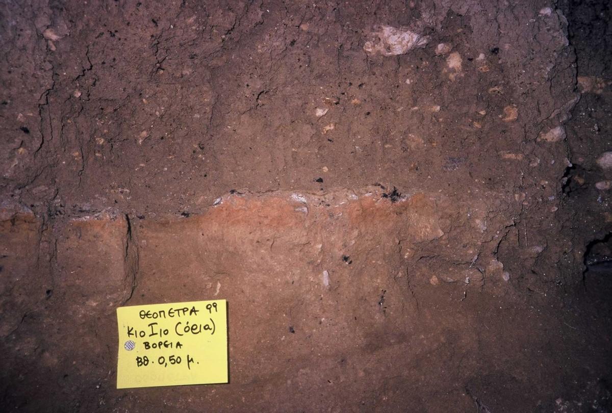 Εικ. 19. Νεολιθική επίχωση επάνω, μεσολιθική κάτω. Τις χωρίζει δάπεδο μεσολιθικού ερυθρού χρώματος με κάρβουνα.