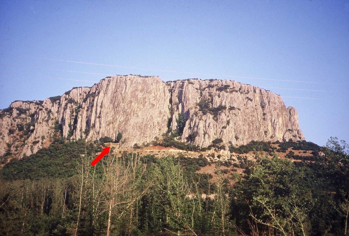 Εικ. 1. Ο βράχος της Θεόπετρας. Η θέση της εισόδου του σπηλαίου σημειώνεται με βέλος.