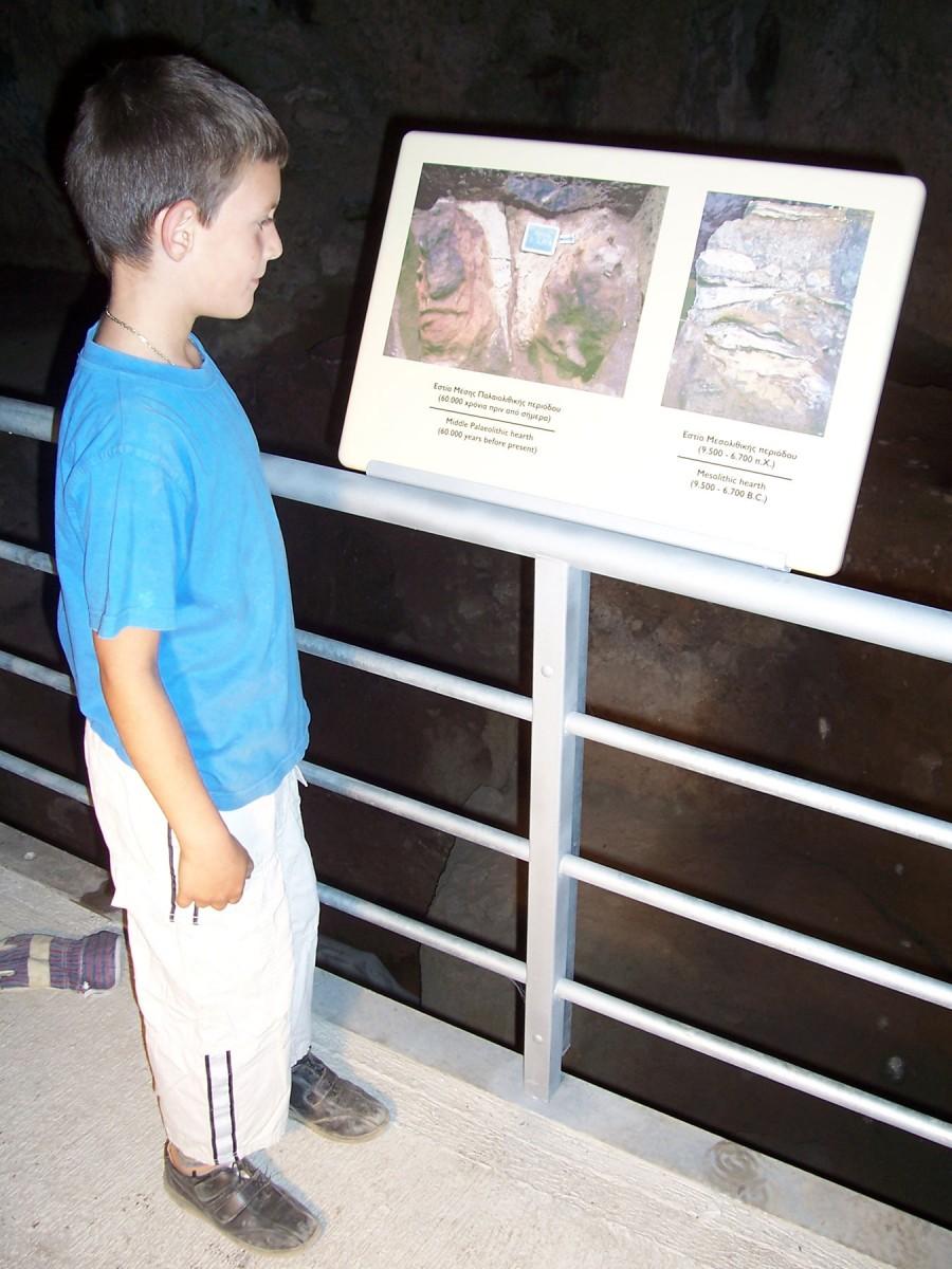 Εικ. 4. Μικρός μαθητής που ενημερώνεται από τις πινακίδες πληροφόρησης μέσα στο σπήλαιο.