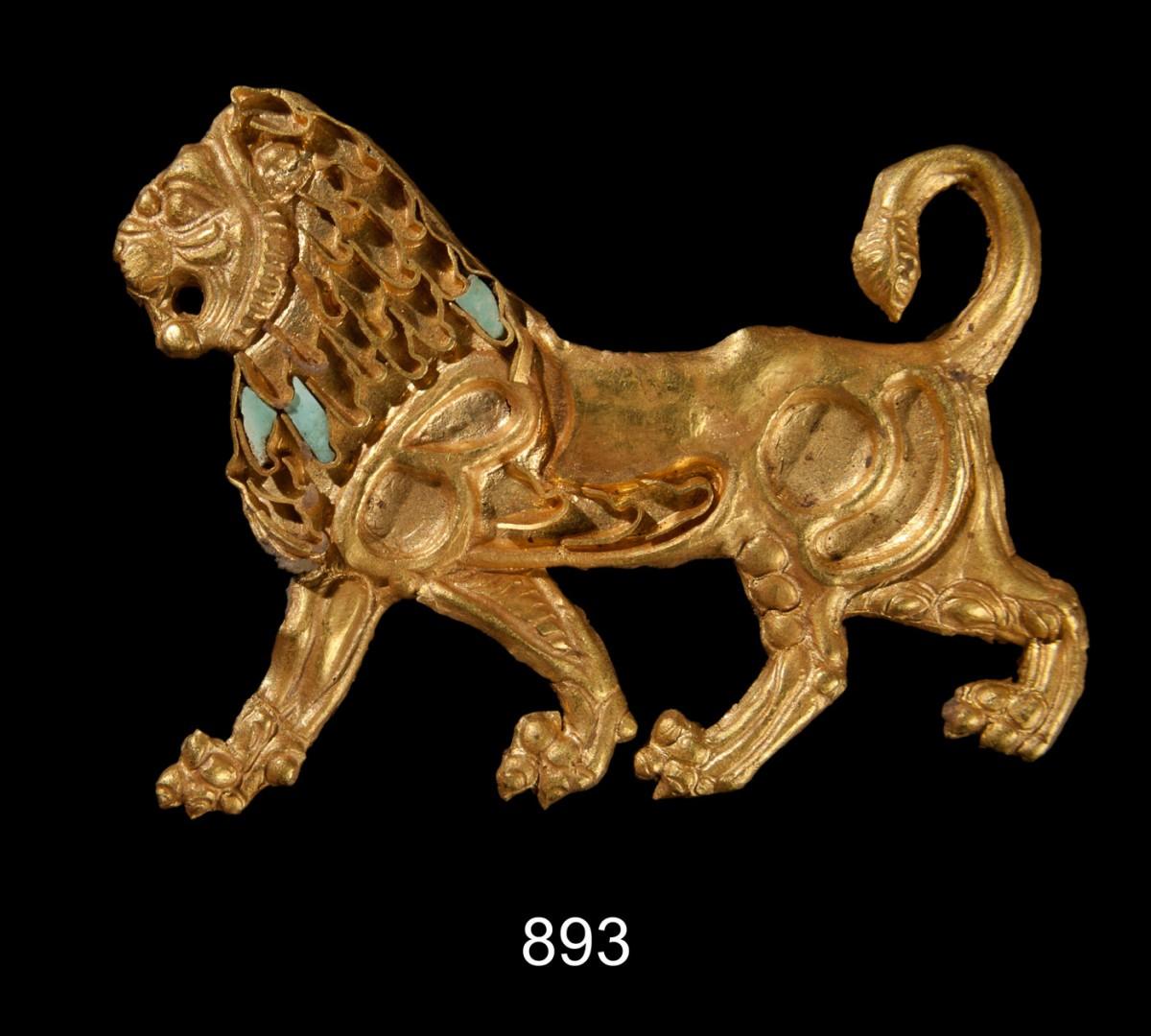 Χρυσό έλασμα σε μορφή λιονταριού, αρχικά ραμμένο σε ύφασμα. Πιθανώς ήλθε ως λάφυρο από την Περσία και αφιερώθηκε στους Μεγάλους Θεούς από κάποιον στρατιώτη του Μεγάλου Αλεξάνδρου μετά την επιστροφή του από την εκστρατεία. 4ος αι. π.Χ.