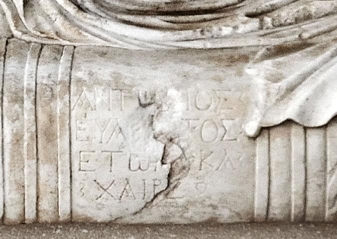 Το αποχαιρετιστήριο επίγραμμα στο κάλυμμα της σαρκοφάγου του Αντωνίου: «AΝΤΩΝΙΟΣ / ΕΥΑΡΕΣΤΟΣ / ΕΤΩΝ ΚΑ / ΧΑΙΡΕ». Αρχαιολογικό Μουσείο Ηγουμενίτσας.