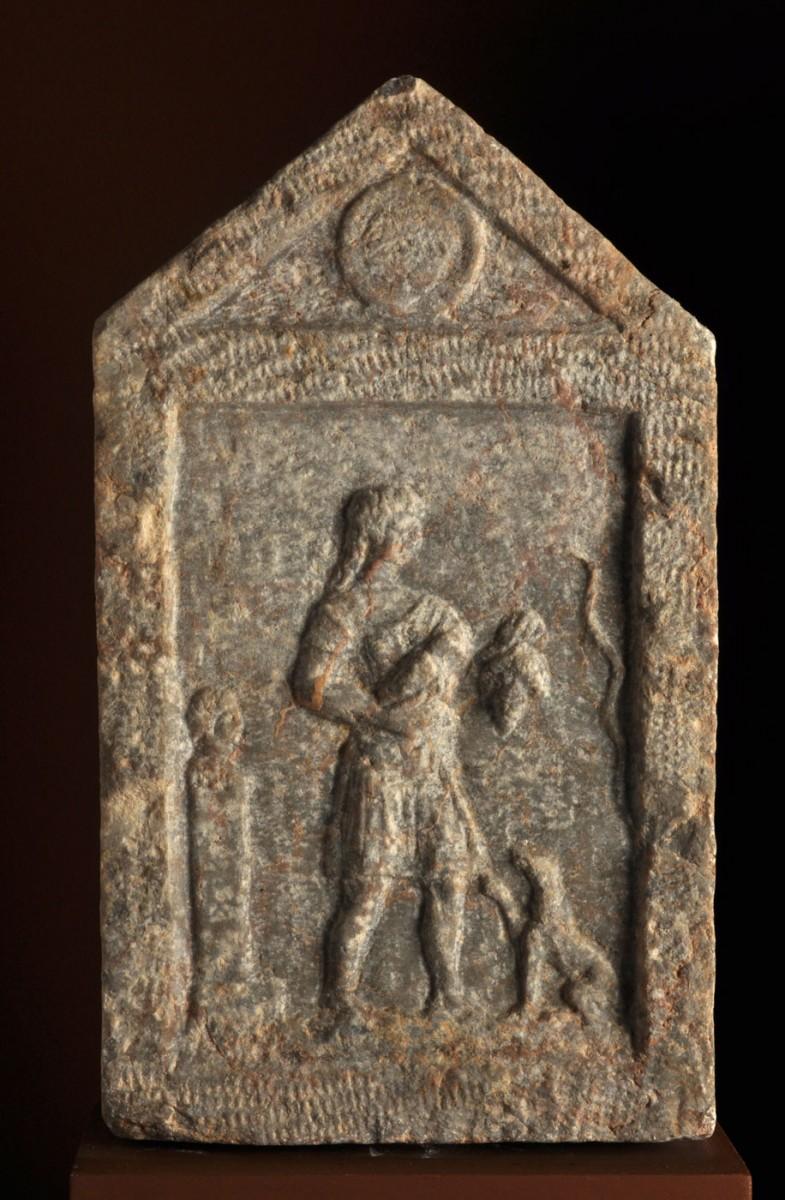 Εικ. 33. Μαρμάρινη επιτύμβια ανάγλυφη στήλη με αετωματική επίστεψη. Απεικονίζει γεωργό ανάμεσα σε ερμαϊκή στήλη, σκύλο και φίδι. Κρατά πτηνό και τσαμπί σταφύλι. Στο τύμπανο του αετώματος ασπίδα. Ελληνιστικοί χρόνοι. Πόλη της Χίου (Βιβλιοθήκη Κοραή).