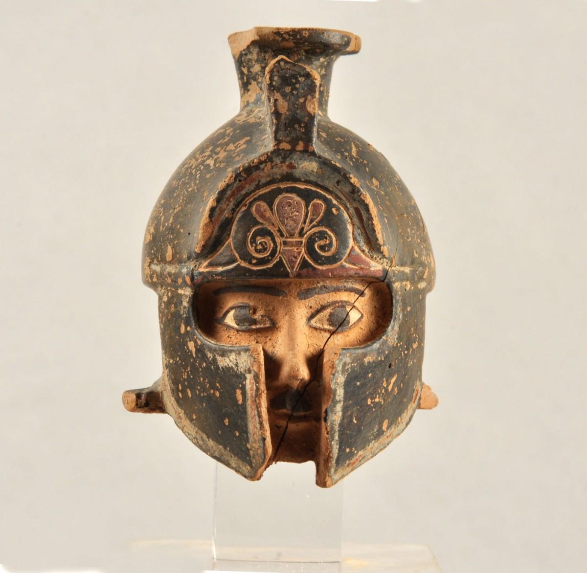 Εικ. 36. Αρύβαλλος σε σχήμα κεφαλής πολεμιστή με κράνος. 600 π.Χ. Εμποριό (Ιερό του Λιμανιού).