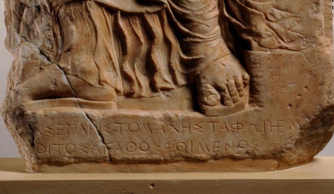 Στο κάτω μέρος της στήλης της Αριστομάχης υπάρχει αποσπασματικά σωζόμενο επίγραμμα (λεπτομέρεια).