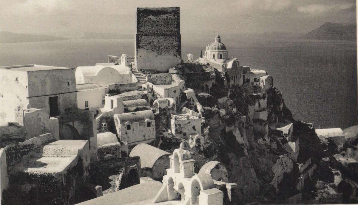 Εικ. 6. Φωτογραφία της περιοχής του καστελλίου, πριν από το σεισμό του 1956. Μπροστά στο γουλά διακρίνεται ο ναός της Αγ. Θεοδοσίας (4) που σήμερα δεν σώζεται, ενώ πίσω του ο μεταγενέστερος ναός της Παναγίας Πλατσανής. Αριστερά διακρίνεται χαρακτηριστικό κτίριο οχυρωματικού χαρακτήρα. Πηγή: Τσίτουρας, 2014, 42.