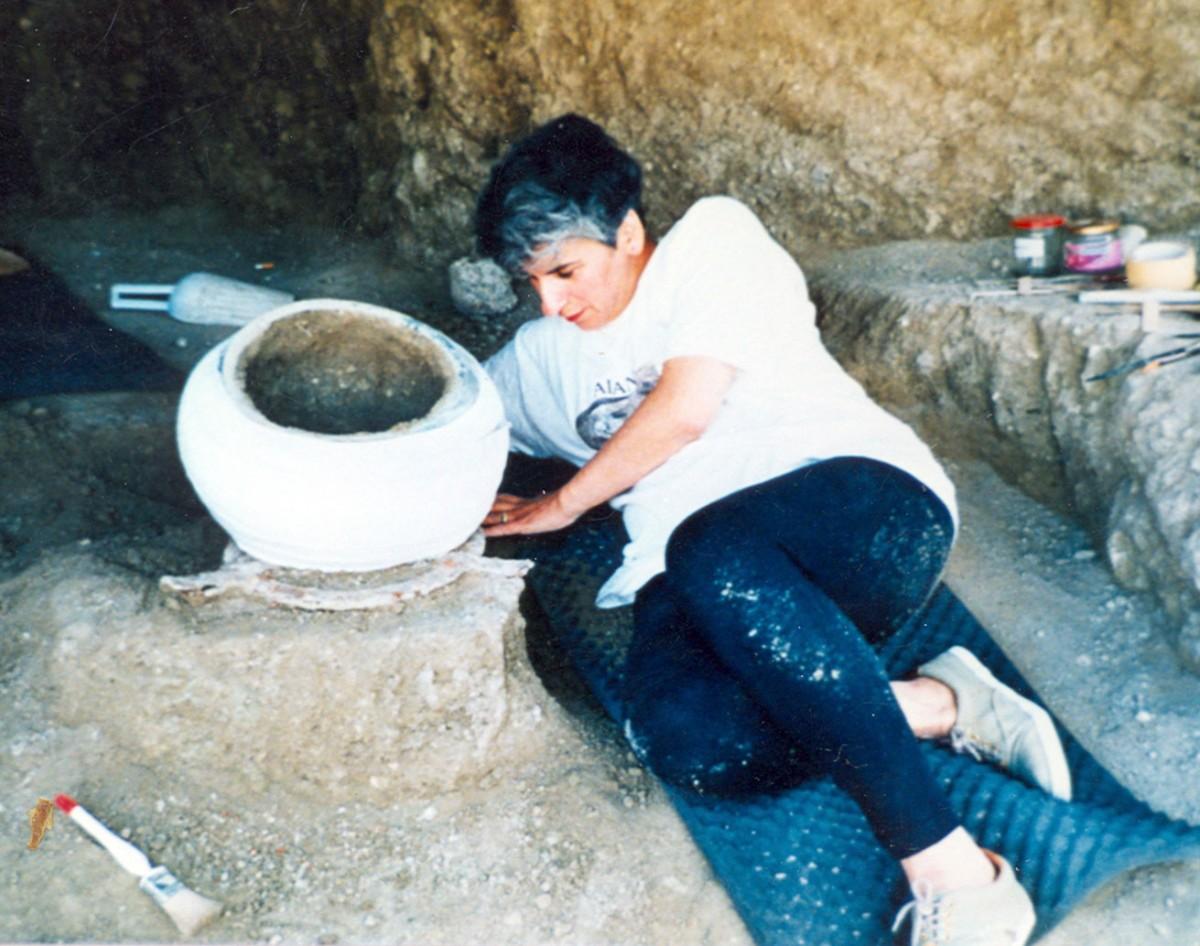 Εικ. 5. Η Μαρίνα Λυκιαρδοπούλου–Πέτρου στην Αρχαία Νεκρόπολη της Αιανής. Χάλκινος λέβης, Αρχαϊκής εποχής, ενισχύεται με γάζες και ελαστικούς επιδέσμους για να απομακρυνθεί από το έδαφος με ασφάλεια (1992).