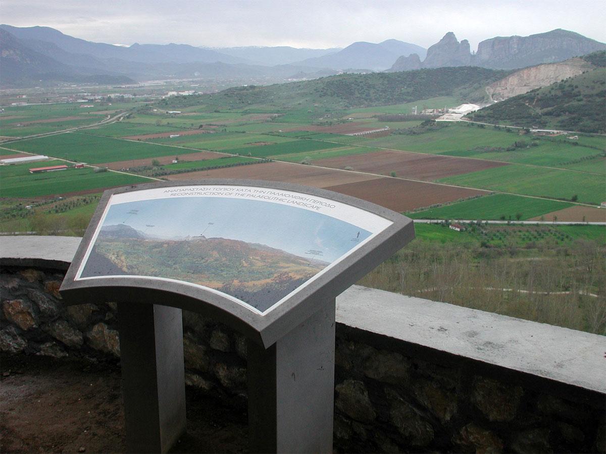 Πινακίδα εξωτερικά του σπηλαίου ενημερώνει για τη μορφή του περιβάλλοντος κατά την Παλαιολιθική περίοδο, πριν τις νεότερες επεμβάσεις. Στο βάθος διακρίνονται τα Μετέωρα και το κατέβασμα του Πηνειού ποταμού.