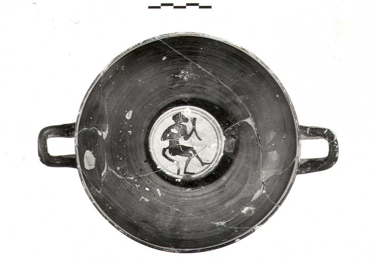 Εικ. 4γ. Παράδειγμα κτερισμάτων εισηγμένων από την Αττική (α΄ τέταρτο 5ου αι. π.Χ.). Μελανόμορφη κύλικα Κ.3555 με παράσταση από τον διονυσιακό κύκλο. Στο μετάλλιό της απεικονίζεται ονοκέφαλος Σάτυρος που κρατά κέρας, από τον ΠΘ.LXΙ. (Από το φωτογραφικό αρχείο της ΙΔ΄ΕΠΚΑ).