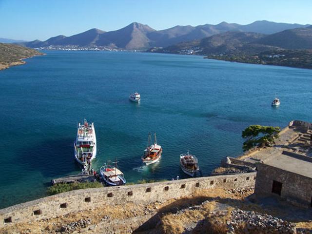 Άποψη της προβλήτας της Σπιναλόγκας από ψηλά, με καράβια που μεταφέρουν τους επισκέπτες (©Εφορεία Αρχαιοτήτων Λασιθίου).