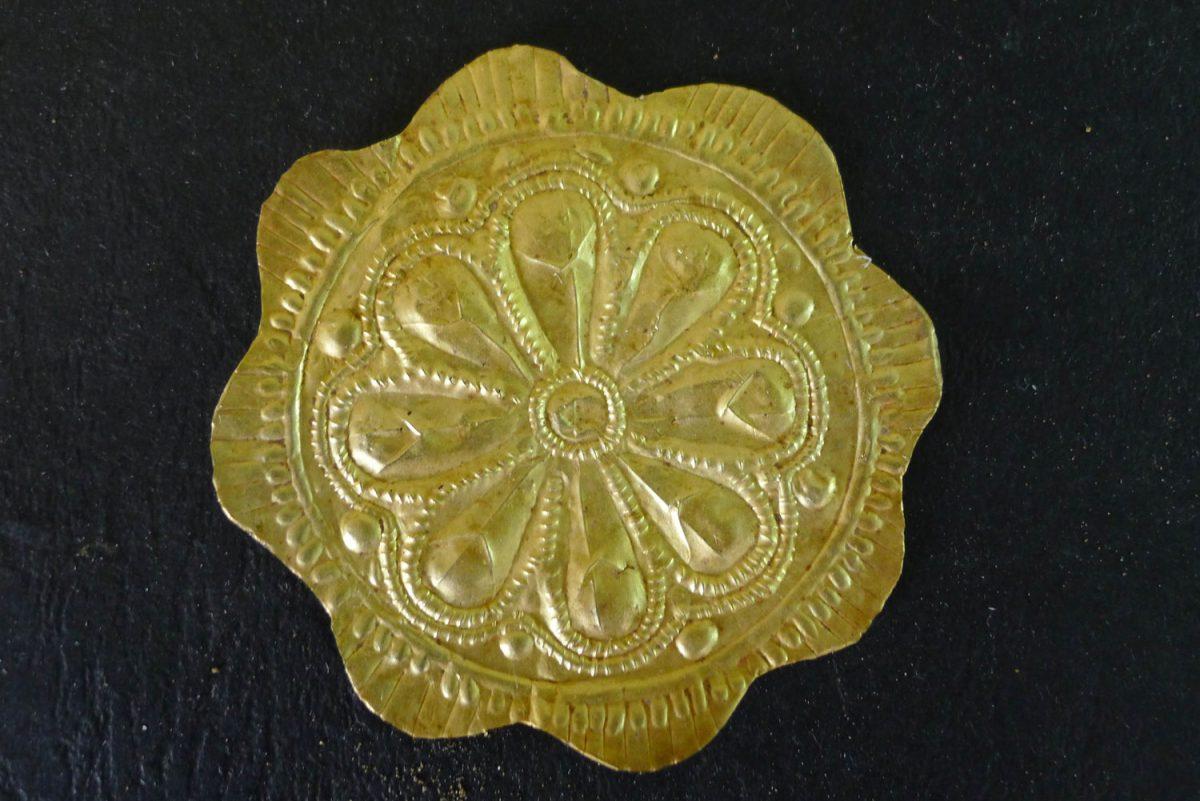 Χρυσός ρόδακας που βρέθηκε στο ύψος του στήθους του νεκρού. Φωτ.: Εφορεία Αρχαιότητων Φλώρινας.