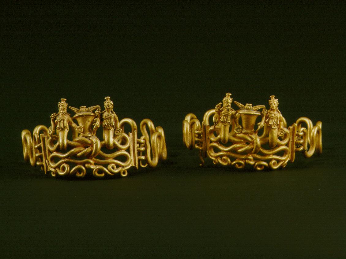 Εικ. 4. Χρυσά βραχιόλια με διαπλεκόμενα σώματα φιδιών που καταλήγουν στις μορφές της Ίσιδος και του Σαράπιδος. Ανάμεσά τους, ένα καλάθι γεμάτο με καρπούς μήκωνος και στάχυα σιταριού παραπέμπει στα μυστήρια του Διονύσου και της Δήμητρας. 1ος αι. μ.Χ. Μουσείο Μπενάκη Ελληνικού Πολιτισμού 1720 και 1721. © Μουσείο Μπενάκη.