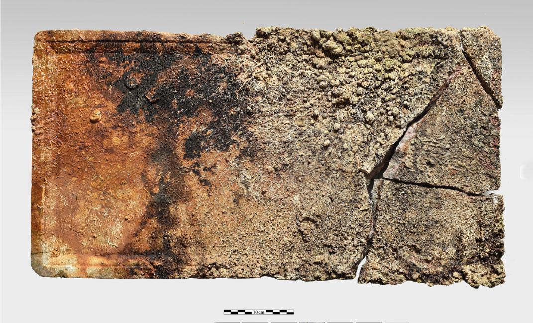 Ορθογώνια πρακτικώς ακέραιη πλάκα από πολύχρωμο ερυθρωπό μάρμαρο, από επίστεψη τράπεζας με περιχείλωμα στην κυρία όψη, διαστάσεων 68x35 εκ., πάχους 5 εκ. (φωτ. ΥΠΠΟΑ).