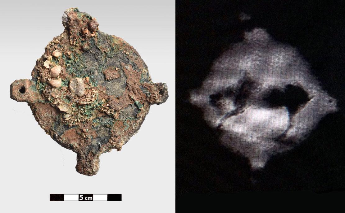 Χάλκινο δισκοειδές αντικείμενο, με τέσσερις διάτρητες αποφύσεις, πάνω στο οποίο, όπως έδειξε η ραδιογραφία, υπάρχει παράσταση ζώου, πιθανόν βοοειδούς (φωτ. ΥΠΠΟΑ).