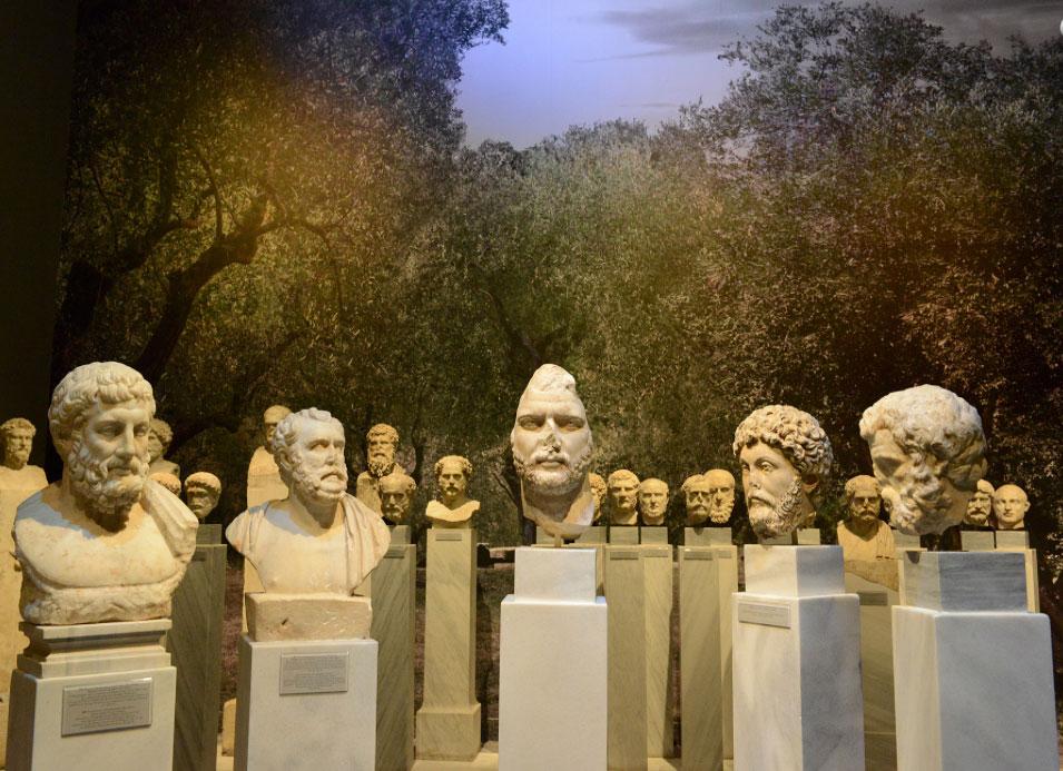 Η εικονιστική προτομή του Αδριανού σε μια ιδεατή συνομιλία με τον Επικούρειο φιλόσοφο Μητρόδωρο (331/0-278/7 π.Χ.), τους δύο αντιπροσώπους της Δεύτερης Σοφιστικής Αντώνιο Πολέμωνα (88-145 μ.Χ.) και Ηρώδη του Αττικού (101-178 μ.Χ.), καθώς και τον Ρωμαίο Αυτοκράτορα και Στωικό φιλόσοφο Μάρκο Αυρήλιο (161-180 μ.Χ.). Στο βάθος οι προτομές και κεφαλές των «Κοσμητών» παρακολουθούν τον νοητό διάλογο (© TAΠΑ/Εθνικό Αρχαιολογικό Μουσείο).