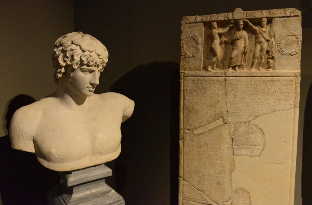 Εικονιστική προτομή του Αντίνοου, από την Πάτρα (130-138 μ.Χ.). Δίπλα της στήλη με κατάλογο των αξιωματούχων του Γυμνασίου και των εφήβων κατά φυλές. Από την Αθήνα. Γύρω στο 212/213 μ.Χ. (© TAΠΑ/Εθνικό Αρχαιολογικό Μουσείο).
