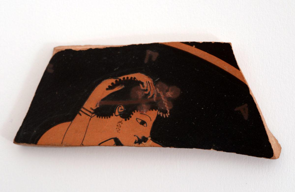 Θραύσμα ερυθρόμορφης κύλικας, από τις επιχώσεις των ανασκαφών του Βράχου της Ακρόπολης. Τέλη 6ου αι. π.Χ. Διατηρείται η κεφαλή αγένειου νεαρού άνδρα και τα χέρια της συντρόφου του που του χαϊδεύουν τα μαλλιά. Τα χείλη τους είναι έτοιμα να συναντηθούν στη διαχρονική και τόσο γνώριμη απεικόνιση ενός ερωτικού φιλιού. (© TAΠΑ/Εθνικό Αρχαιολογικό Μουσείο)
