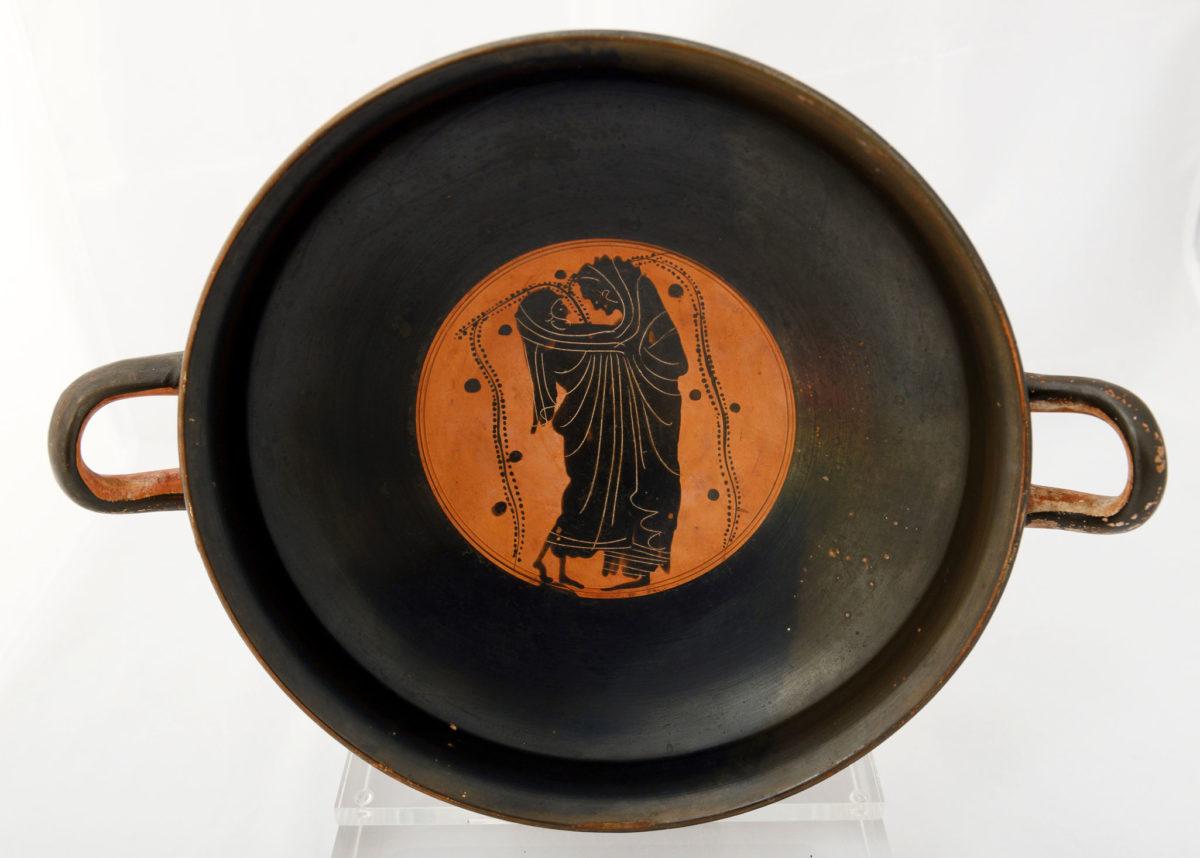 Μελανόμορφη κύλικα. Άγνωστης προέλευσης. 490-480 π.Χ. Στο μετάλλιο της κύλικας εικονίζεται ερωτικό ζευγάρι, τυλιγμένο στο ίδιο ιμάτιο. (© TAΠΑ/Εθνικό Αρχαιολογικό Μουσείο)