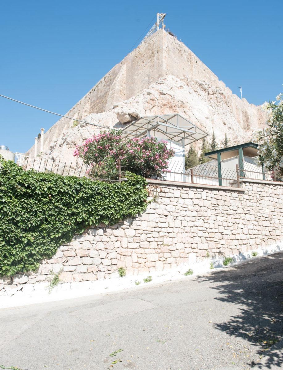 Εικ. 40. Φωτογραφία του τοίχου που επρόκειτο να αντικατασταθεί από την καγκελόφραξη της περίφραξης και πίσω του οι σύγχρονες ογκώδεις και ευτελείς κατασκευές.